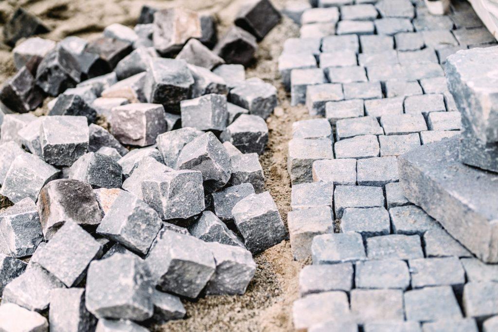 Granite cobblestone pavement details. Construction of pavement roads in progress